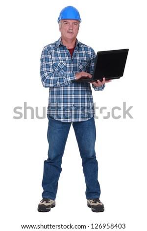 Tradesman holding a laptop - stock photo