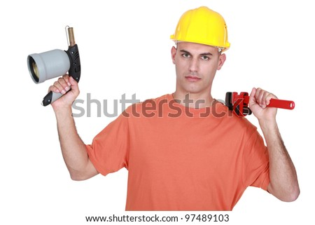 Tradesman holding a pipe wrench and a blowtorch - stock photo