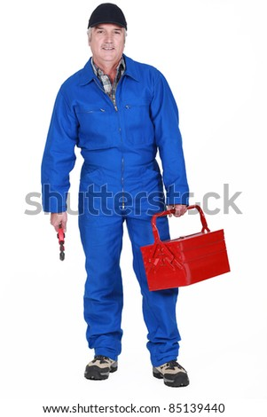 Tradesman holding a tool and his toolbox - stock photo