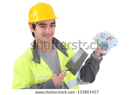 Tradesman holding a trowel and cash - stock photo
