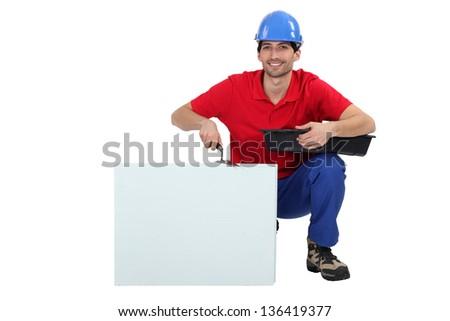 Tradesman kneeling next to a blank sign - stock photo