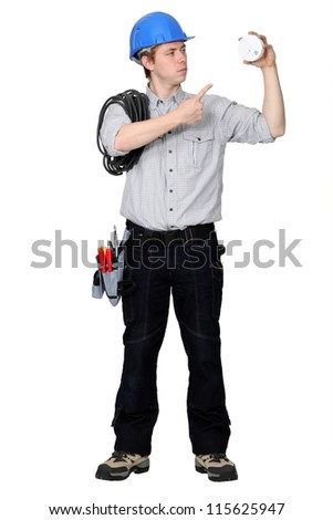 Tradesman pointing to a smoke detector - stock photo