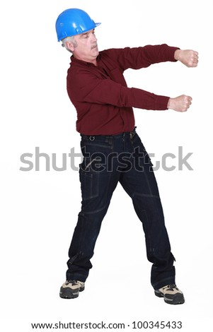 Tradesman pulling on an invisible bar - stock photo