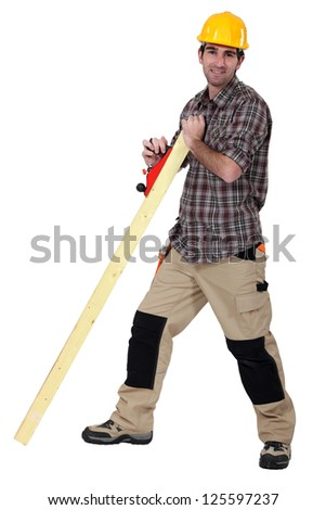 Tradesman smoothing a plank of wood - stock photo