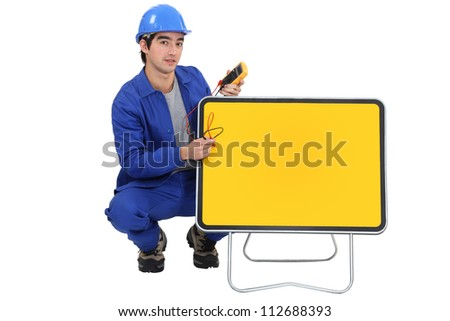Tradesman squatting next to a traffic sign - stock photo