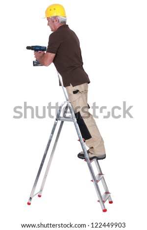 Tradesman standing on a stepladder and using a power tool - stock photo