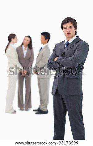 Tradesman with arms folded and associates behind him against a white background - stock photo