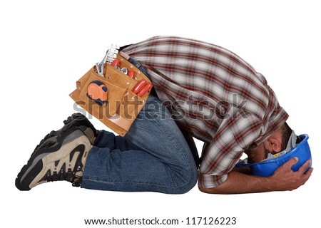 Tradesman with his head in his hands - stock photo