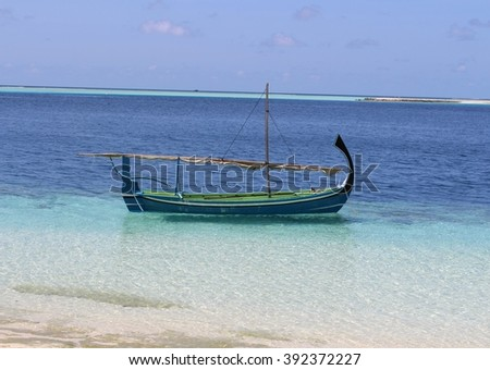 Tradition fishing boat on tropical beach Maldives with blue sky and clear water. - stock photo