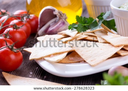 Tradition Mexican Tortilla Chips nachos with handmade guacamole sauce on wooden table - stock photo