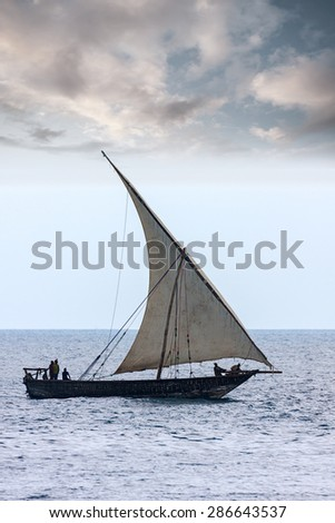 traditional african dhow sailing vessel with full sail to the wind and all hands on deck - stock photo
