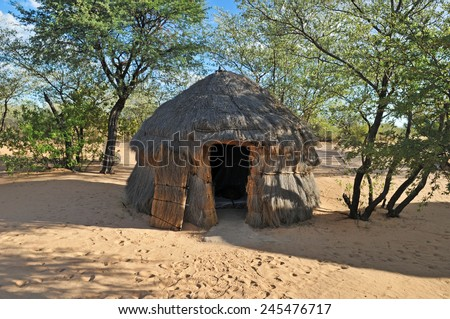 traditional african thatched hut in the Kalahari Desert - stock photo