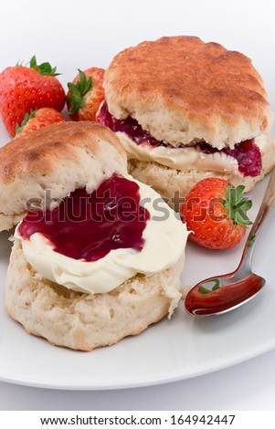Traditional Afternoon Tea of Devonshire scones topped with clotted cream and strawberry jam often served with coffee or tea - stock photo
