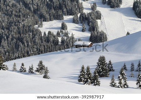 Traditional alpine cabin in the mountains of the Swiss Alps, Switzerland on the side of a pristine snow slope. - stock photo