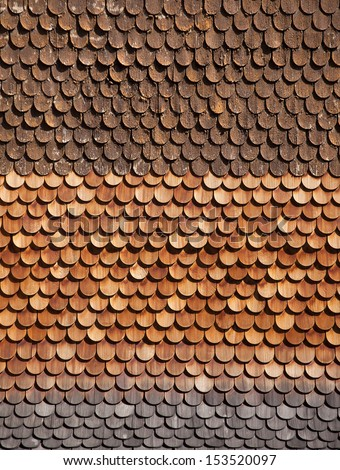 Traditional alpine wooden shingle wall in the sun - stock photo