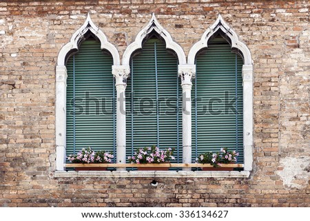 Traditional ancient gothic style window with flower pots in Venice, Italy - stock photo