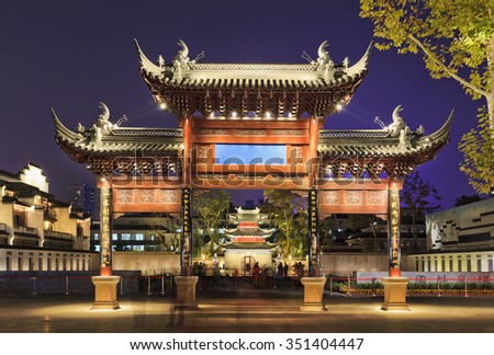 traditional ancient wooded gates in front of confucius temple and education centre in Nanjing, China, at sunset with illumination by street lights - stock photo
