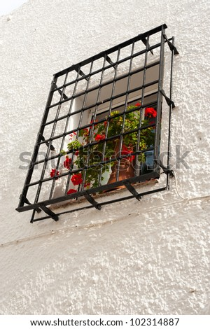 Traditional Andalusian window with red geraniums on the sill - stock photo