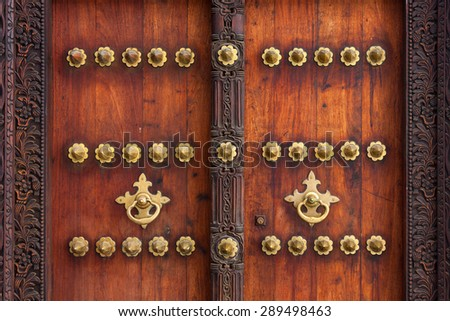 traditional arab zanzibar wooden door and doorway ornately carved and decorated with brass fittings - stock photo