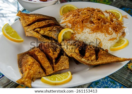 Traditional Arabic mixed rice and grilled fish. - stock photo
