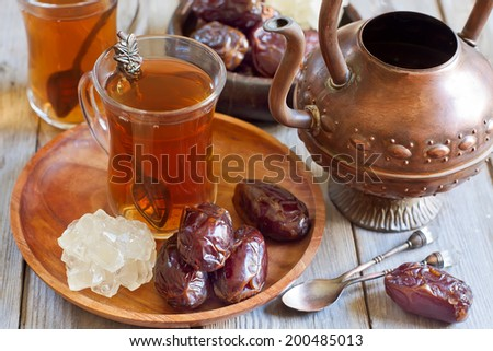 Traditional arabic tea with dry madjool dates and rock sugar nabot. Selective focus. - stock photo
