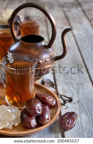 Traditional arabic tea with dry madjool dates and rock sugar nabot. Selective focus. Copy space background. - stock photo