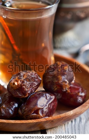 Traditional arabic tea with dry madjool dates. Selective focus. - stock photo