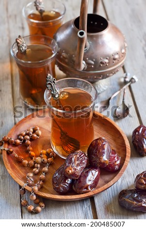 Traditional arabic tea with wood beads, dry madjool dates and rock sugar nabot. Selective focus. - stock photo