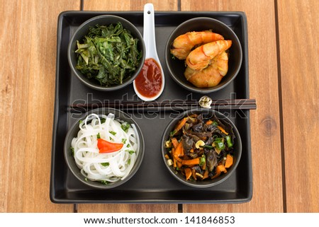 Traditional asian dish on a square plate in black bowls with shrimp, rice noodles, kale (green cabbage) and fried vegetables. Composed with ceramic spoon with spicy red sauce and chinese chopsticks. - stock photo
