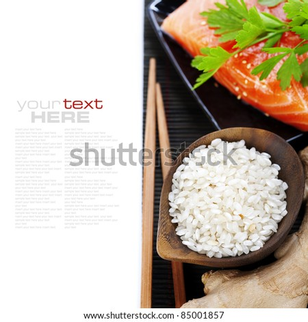 traditional asian ingredients (Fresh salmon steak filet, uncooked rice, ginger and chopsticks) over white with sample text - stock photo