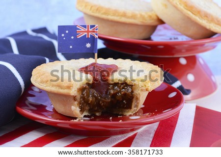 Traditional Australian Meat Pies for Australia or Anzac Day holiday party food, in red, white and blue setting. - stock photo