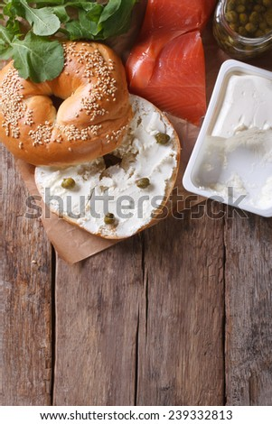 Traditional bagel with salmon and ingredients on the table. top view of the vertical  - stock photo