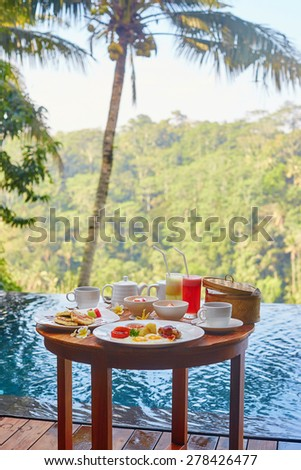 Traditional Balinese breakfast with banana pancake and fresh fruits served near the pool with coconut palm in the background - stock photo