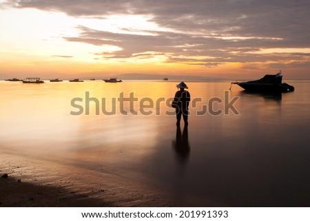 traditional Balinese fisherman fishing on beach on Sanur beach at sunrise, Bali, Indonesia - stock photo