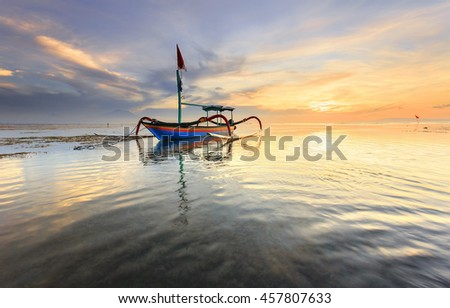 Traditional Balinese fishing boat Jukung during sunrise at Sanur beach in Bali, Indonesia - stock photo