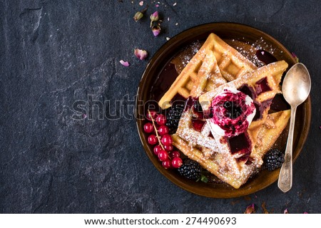 Traditional Belgian waffles with ice cream and berry fruit sauce in the plate,selective focus and blank space - stock photo
