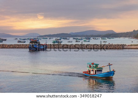 Traditional blue wooden fishing boats in the ocean at sunset, Asia - stock photo