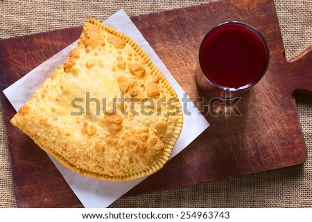 Traditional Bolivian snack called Pastel (deep-fried pastry filled with cheese) served with Api, a purple corn beverage, photographed with natural light (Selective Focus, Focus on the pastry)    - stock photo