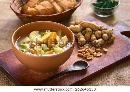 Traditional Bolivian Sopa de Mani (peanut soup) made of meat, pasta, vegetables and ground peanut, photographed on wooden board with natural light (Selective Focus, Focus in the middle of the soup) - stock photo