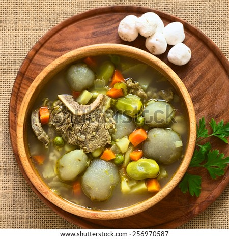Traditional Bolivian soup Chairo de Tunta (tunta is a freeze-dried potato typical in Andean regions) made of tunta, beef, broad bean, pea, carrot, dry tunta on side, photographed with natural light - stock photo