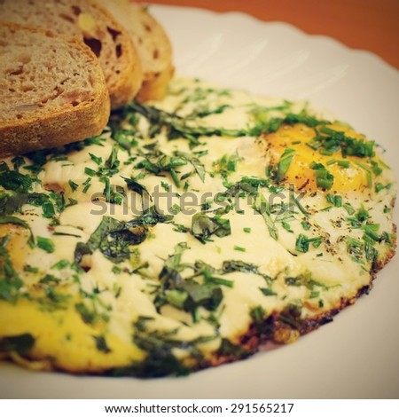 Traditional breakfast with bacon , fried eggs with cheese and herbs. With brown wholemeal bread - stock photo