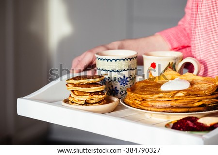 Traditional breakfast with pancakes, sour cream, jam and hot drinks on a tray in the hands of women - stock photo