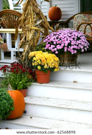 Traditional brick colonial dressed up for fall with colorful mums and harvest gourds - stock photo