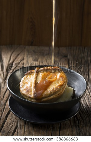 Traditional British meat pie with mashed potatoes. Hot gravy is being poured on the pie. The food is sitting on a rustic wooden background.  - stock photo