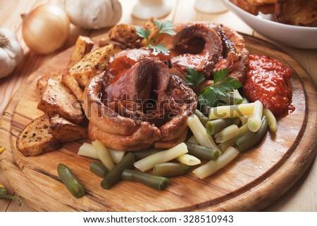 Traditional british sunday roast with yorkshire pudding, roasted potato and vegetables - stock photo