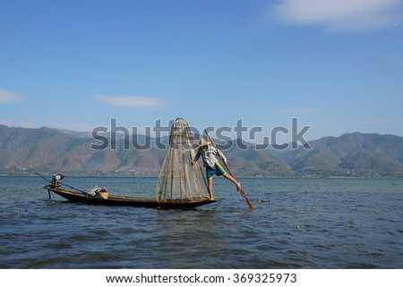 Traditional Burmese fishermen with fishing net at Inle lake in Myanmar famous for their distinctive one legged rowing style - stock photo
