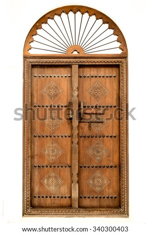 Traditional carved wooden Arab doorway of a restored house in Muharraq, Bahrain.  - stock photo