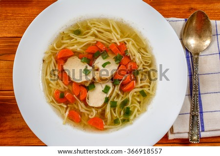 Traditional chicken soup with meat and carrot and noodles on wood table - stock photo