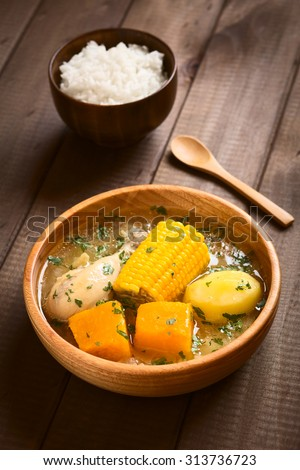 Traditional Chilean Cazuela de Pollo (Cazuela de Ave) soup made of chicken, corn, pumpkin and potato with rice in the back, photographed with natural light (Selective Focus, Focus one third into soup) - stock photo