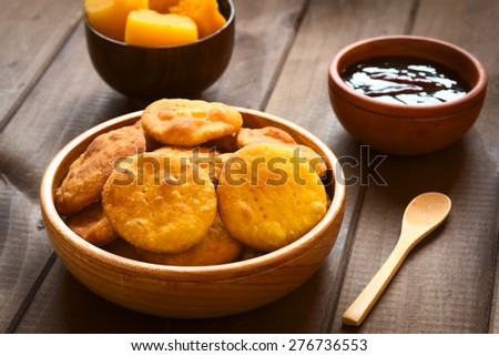 Traditional Chilean Sopaipilla fried pastry made with mashed pumpkin in dough, served with Chancaca sweet sauce, photographed on wood with natural light (Selective Focus, Focus on first sopaipillas) - stock photo